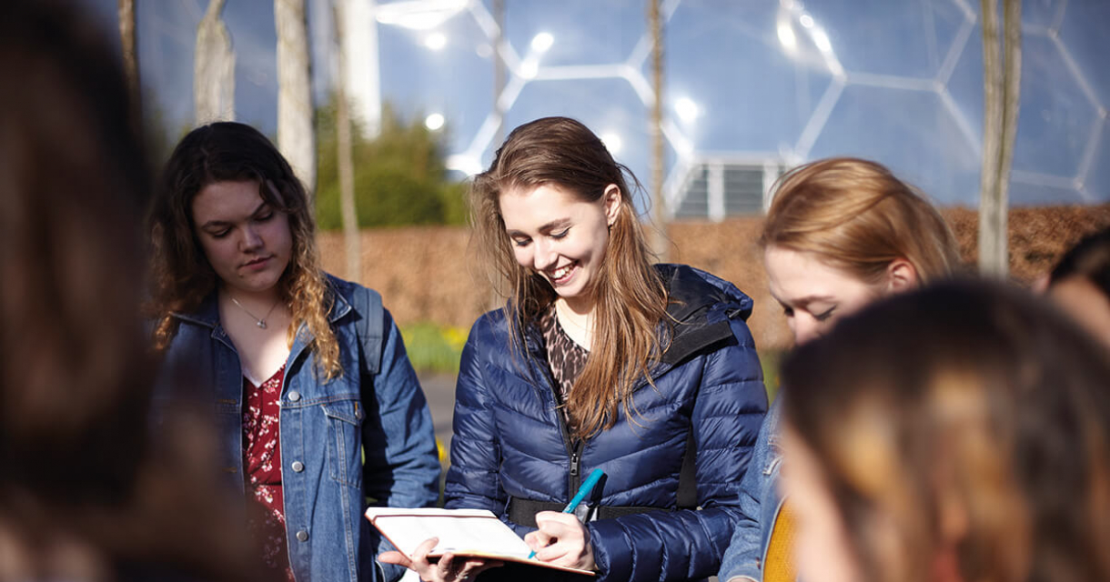 Girl smiling and looking at notebook in hand at the Eden Project.