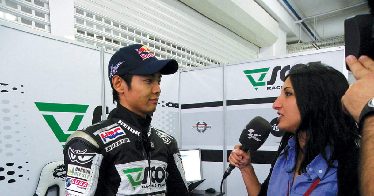 Graduate interviewing racing driver in leathers and Red Bull cap.