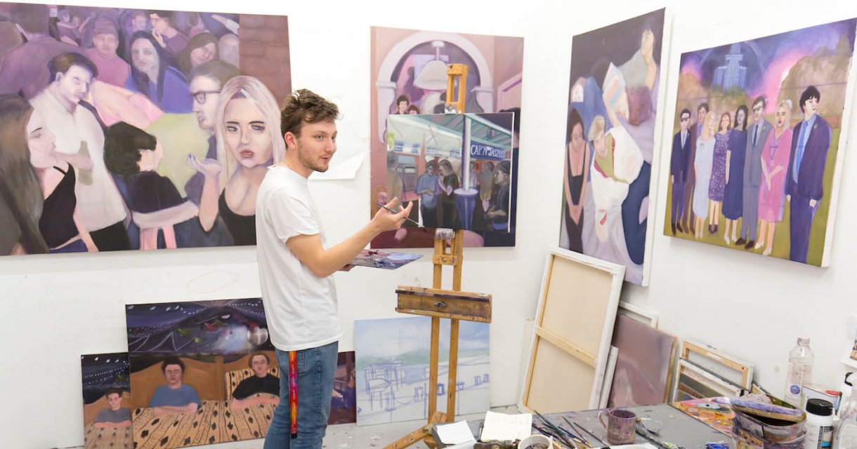 A male student standing at an easel surrounded by paintings