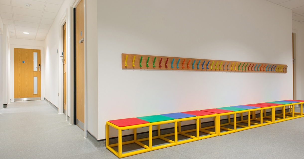 Row of colourful coat hooks and stools.
