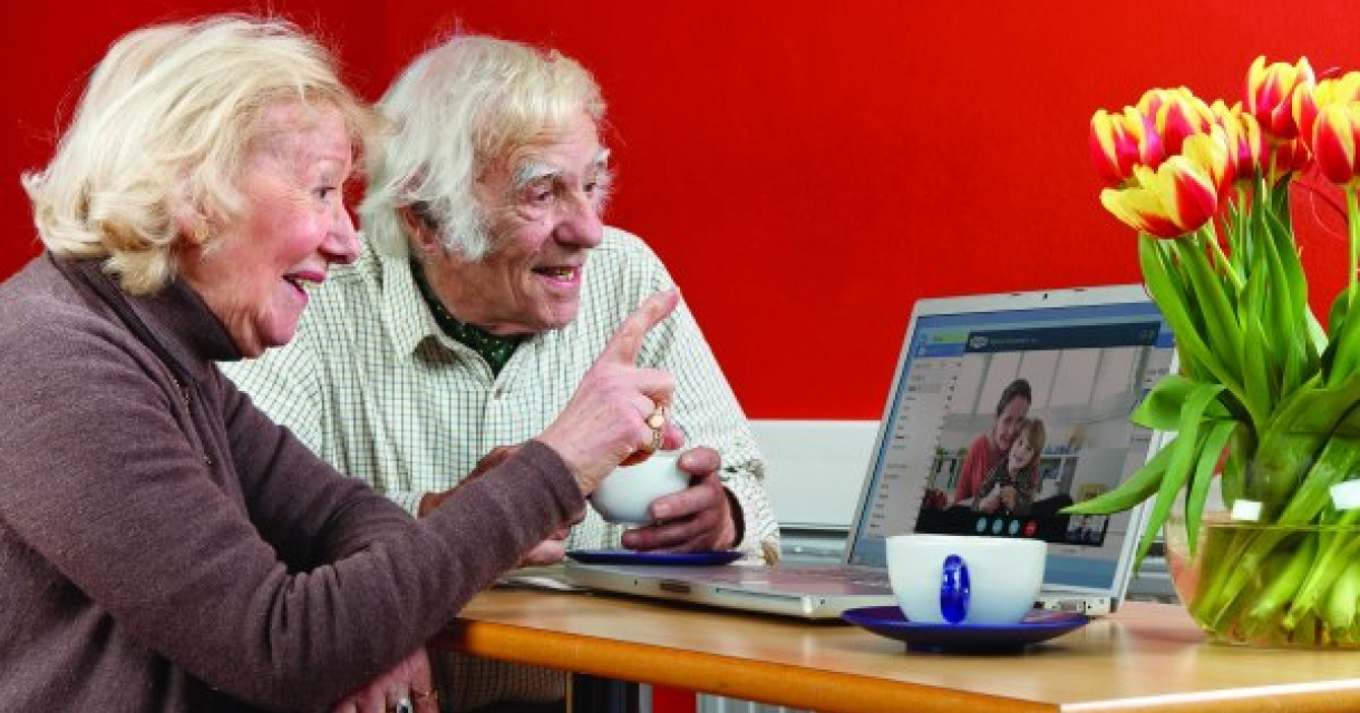 Elderly couple talking to family on a video call on their laptop.