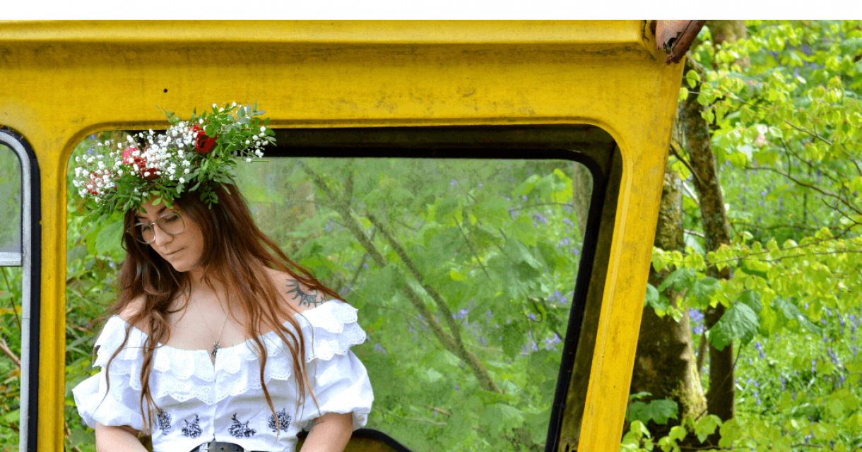 A woman wearing a flower crown sitting on a yellow machine in the woods