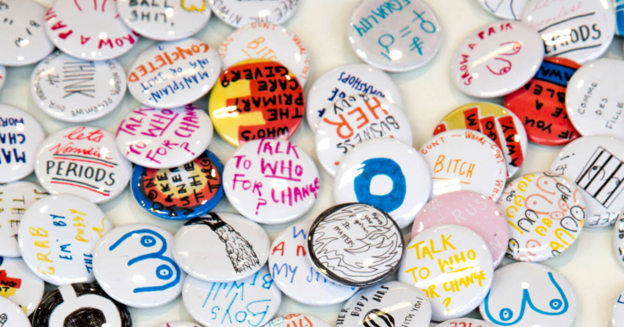 Lot's of badges with handwritten writing on in different colours.