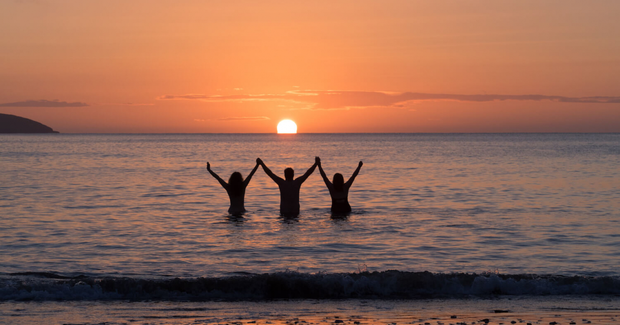 Three Falmouth University students in the sea as the sun is setting