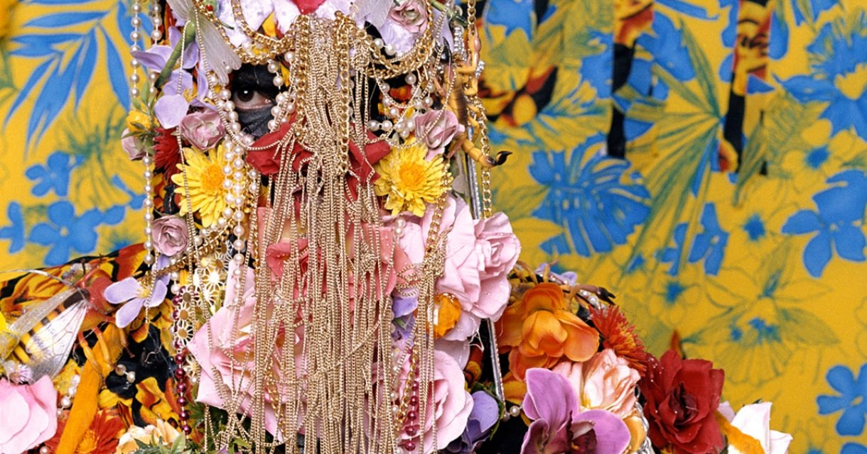 Figure covered in flowers and gold chains with just eyes showing through.
