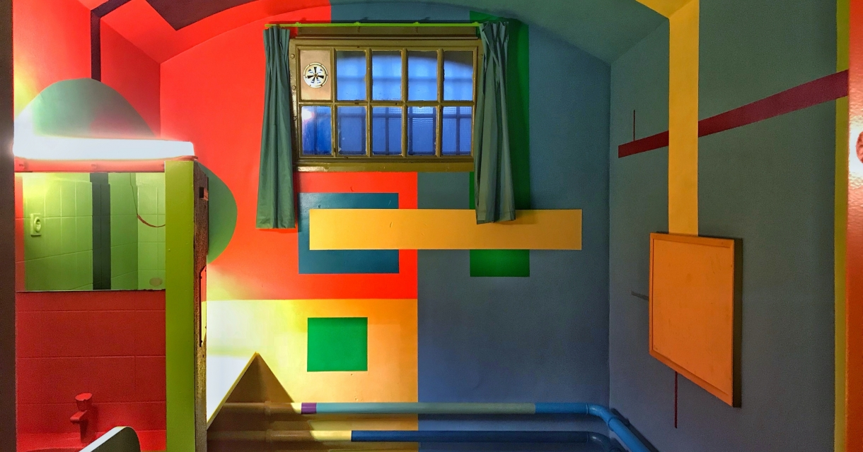 Prison cell painted in bright clocks of colour.