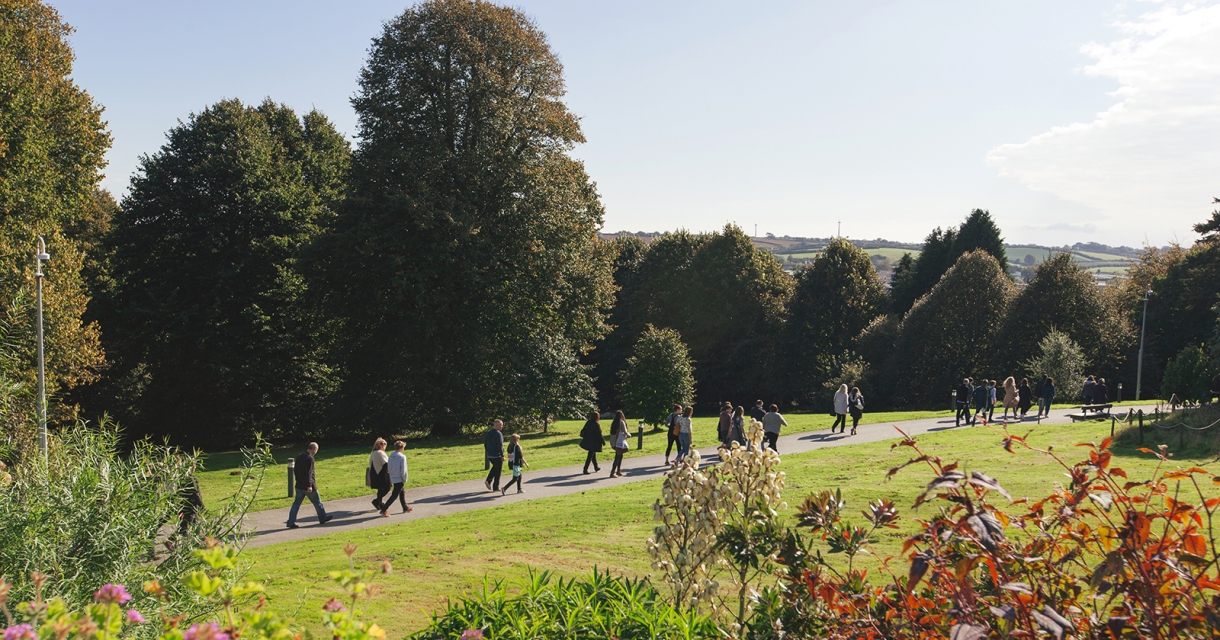 Groups of parents and students walking through penryn gardens on an open day.