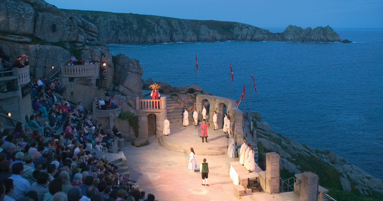 View of the Minack theatre at night, actors on the stage lit up against the dark sea.