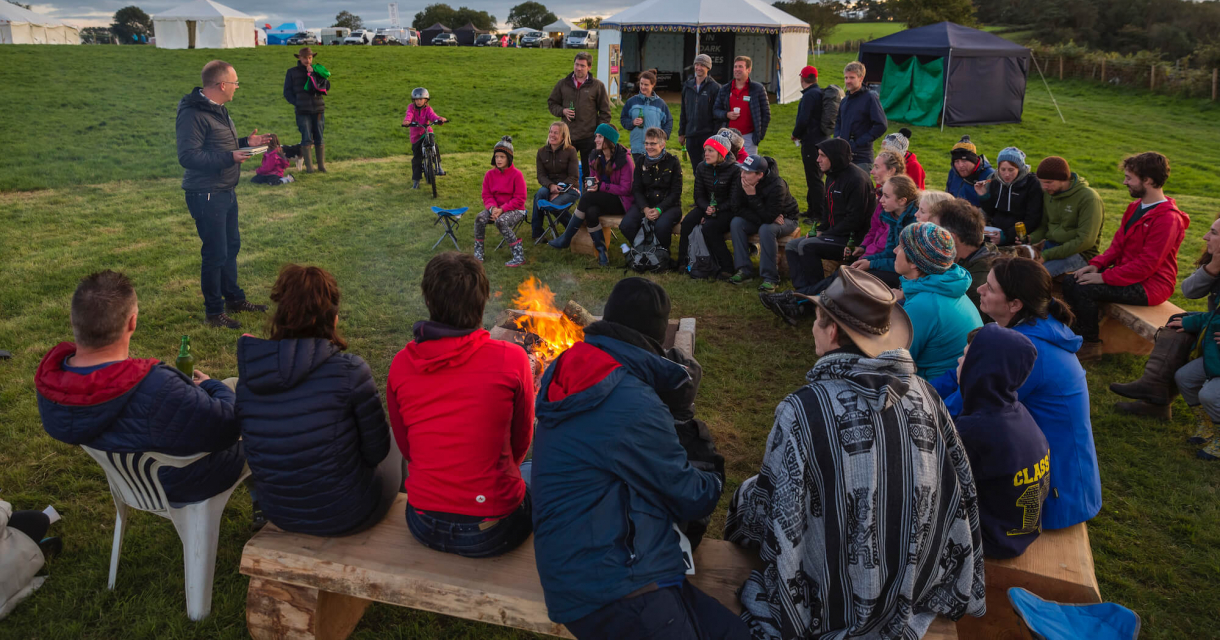 A group sat in a circle with fire in the middle listening to writer, Wyl Menmuir, give a talk.