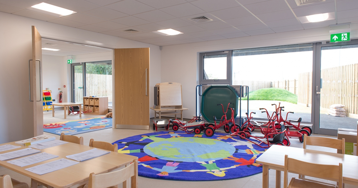 Room with colourful rug and lot's of little red tricycles.