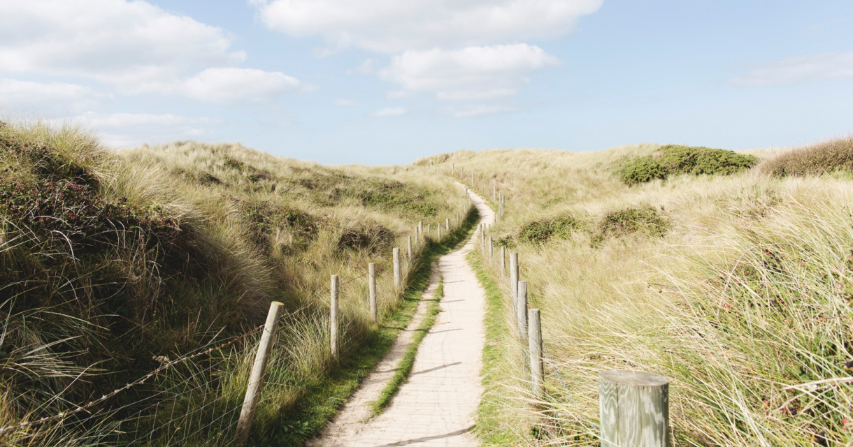 A narrow path through sand dunes with blue sky
