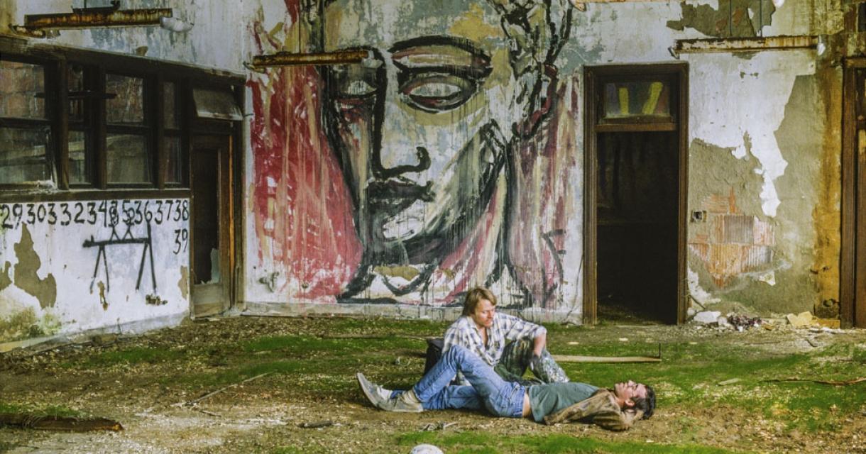 Wojnarowicz reclines with Mike Bidlo. Pier 34, New York, 1983