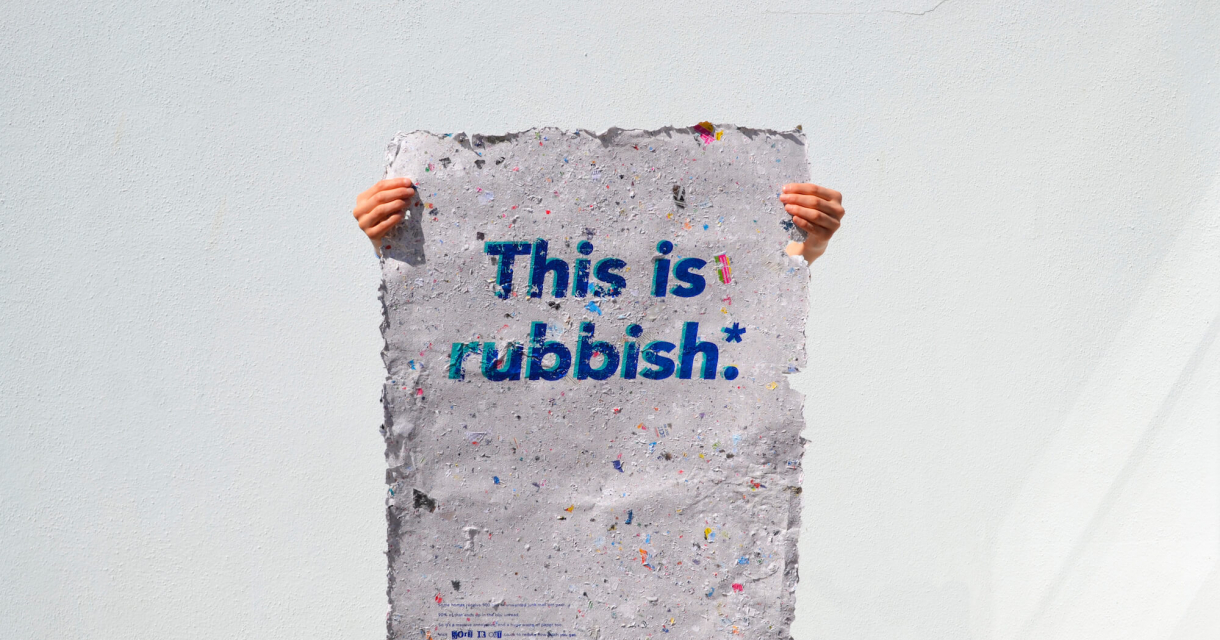 Hands holding a recycled piece of paper with the words this is rubbish on.