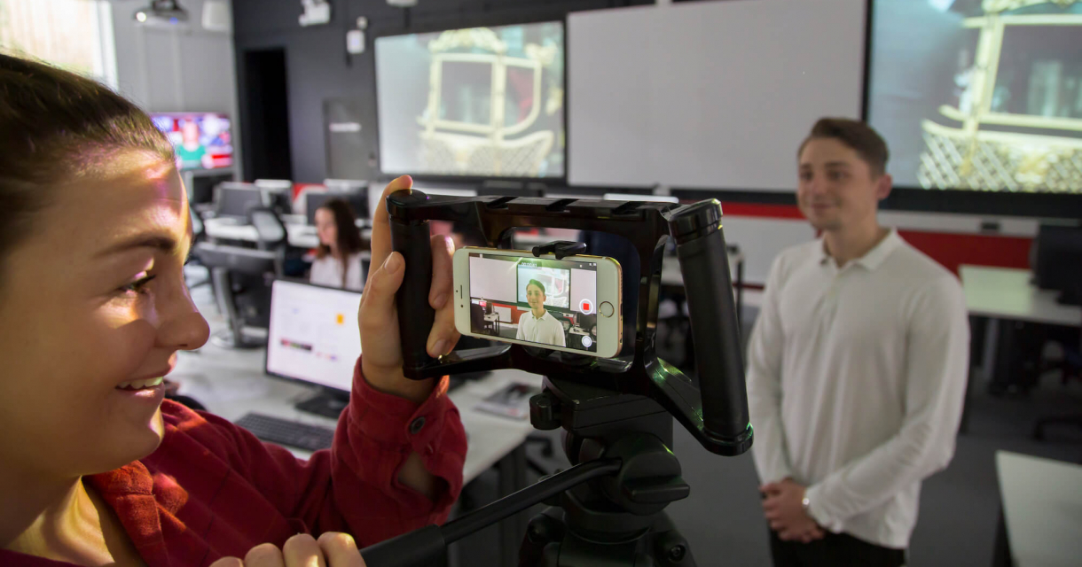 Student filming in the newsroom on a smartphone.