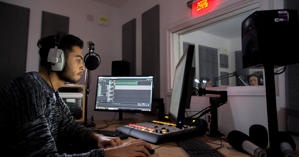 Student wearing headphone while sat in a mixing studio