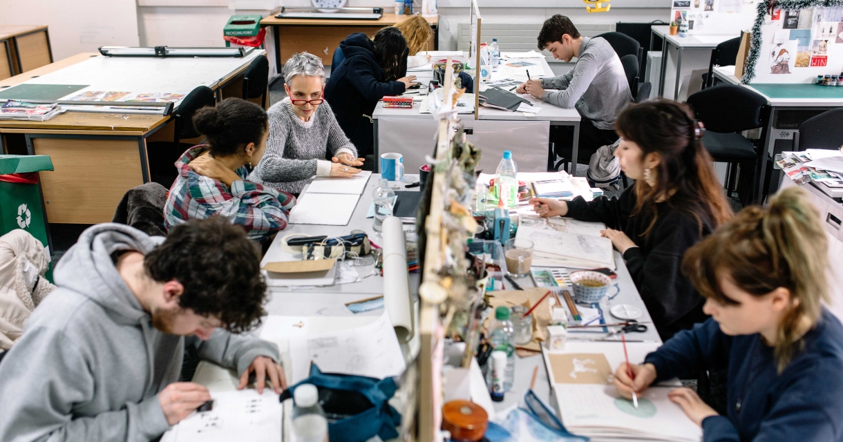 Students in busy studio at desks drawing.