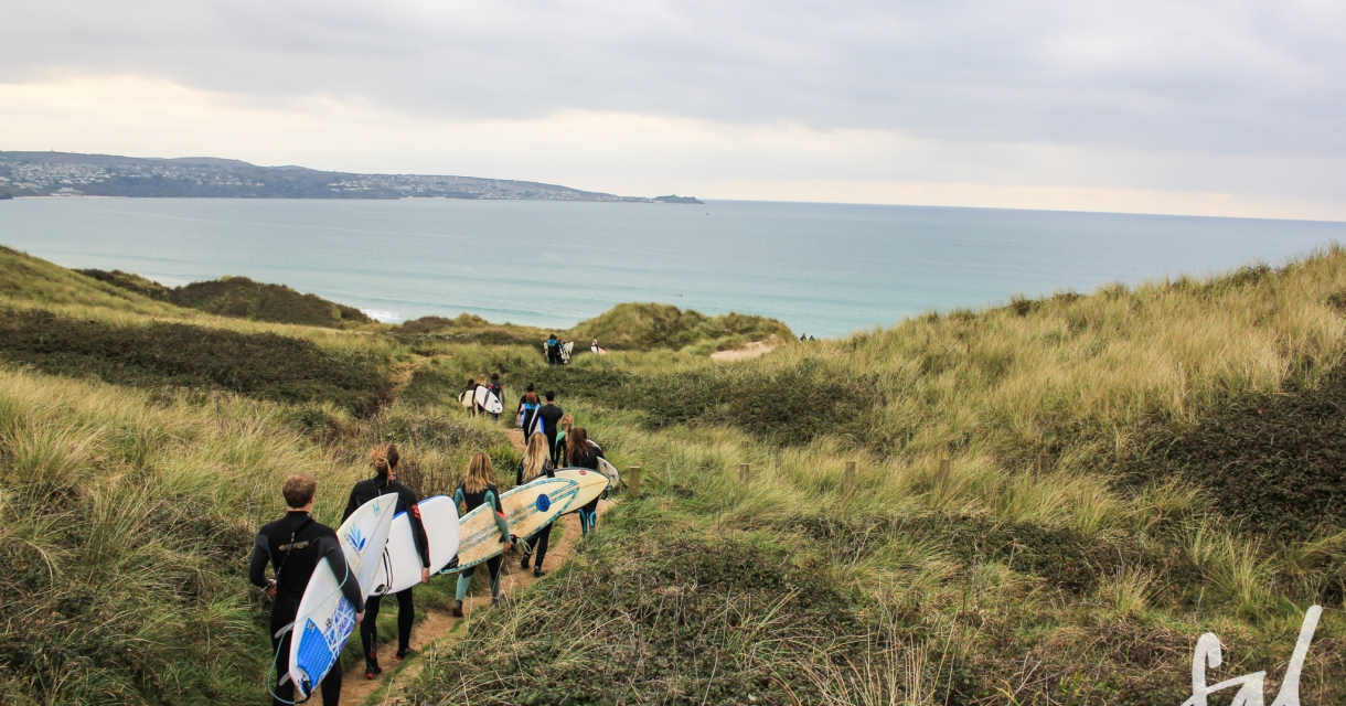 A group of surfers walking down a coast path with surf boards under their arms
