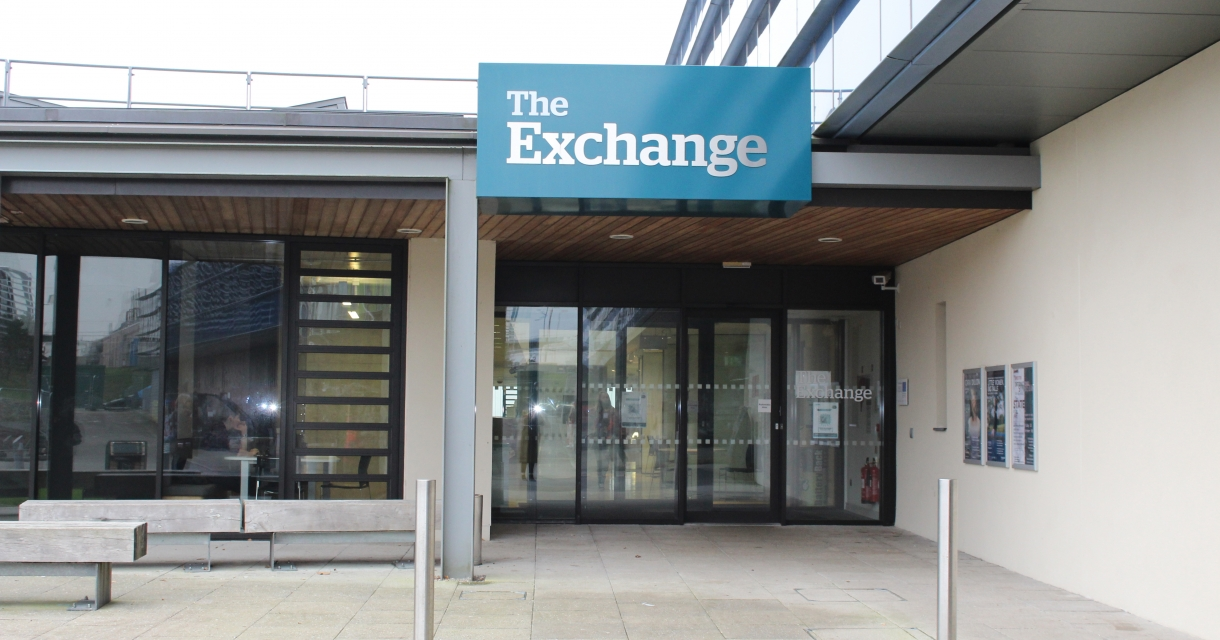 glass fronted building with 'The Exchange' sign on a blue background