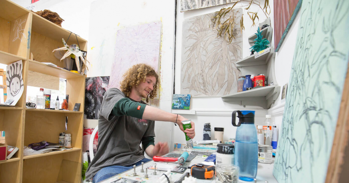 A male student with curly hair sat in a Fine Art studio at Falmouth University