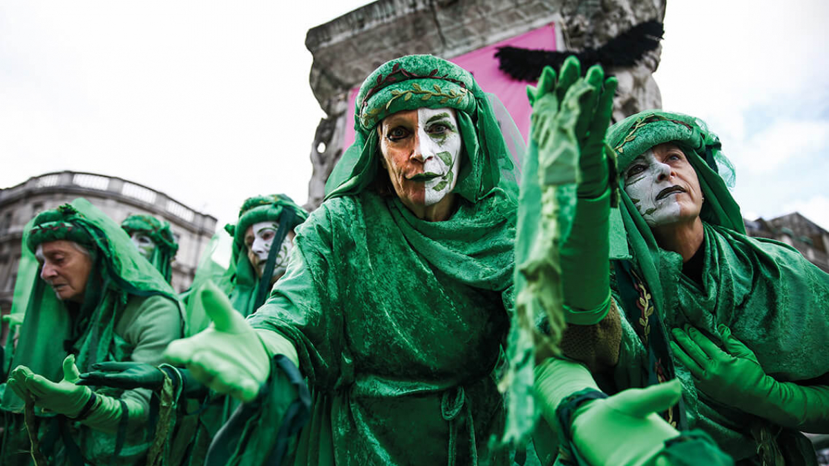 A group of people wearing green cloaks with white painted faces