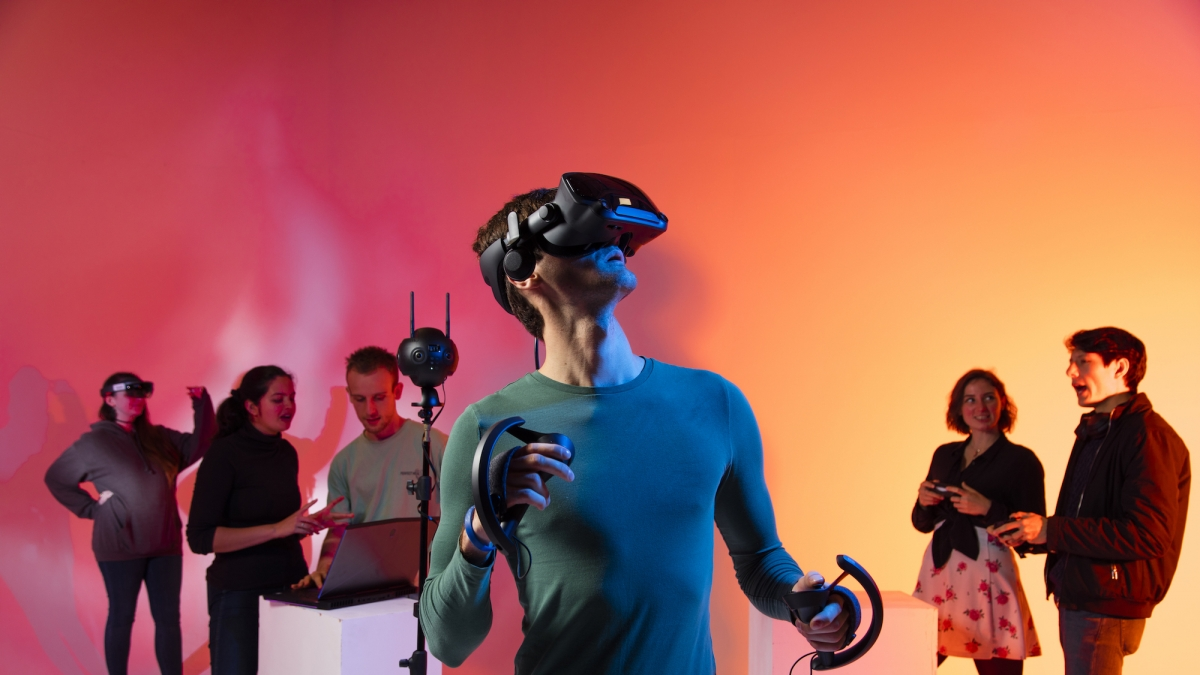 Male student wearing a virtual reality headset with five other students in the background