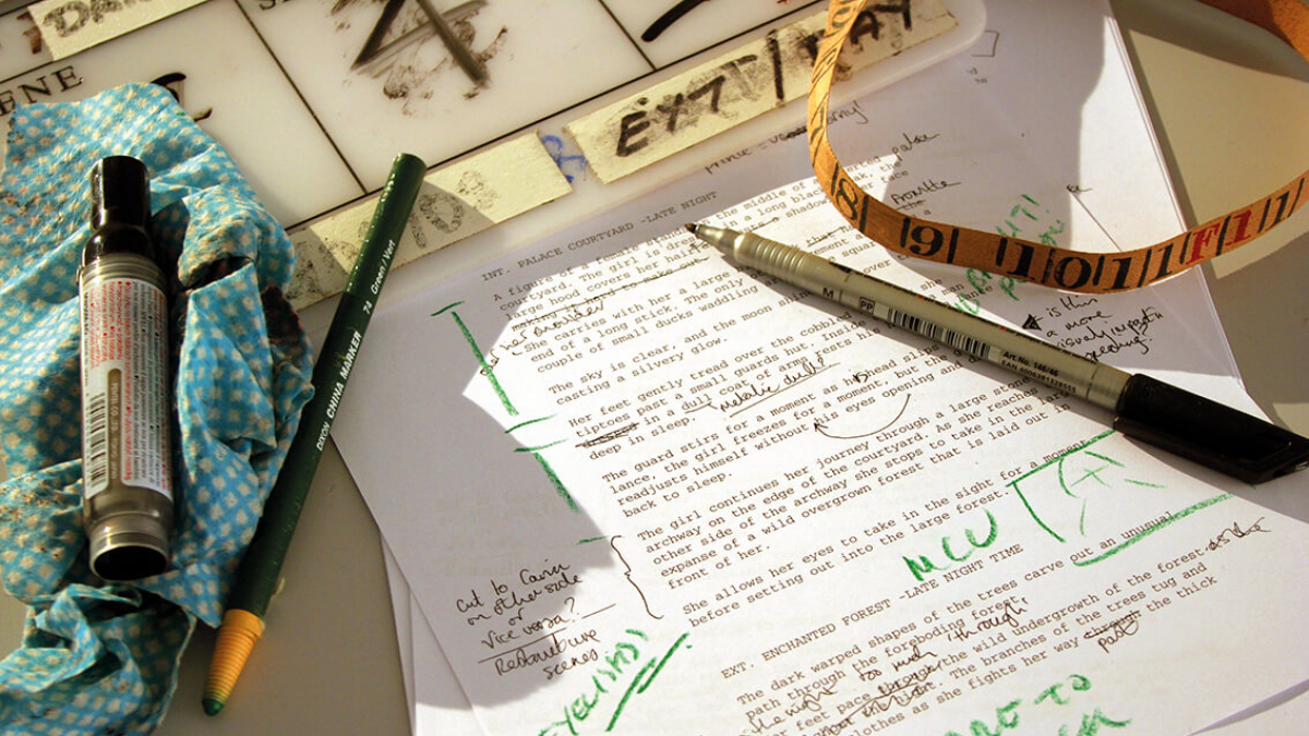 A printed piece of paper with green ink annotations and pens