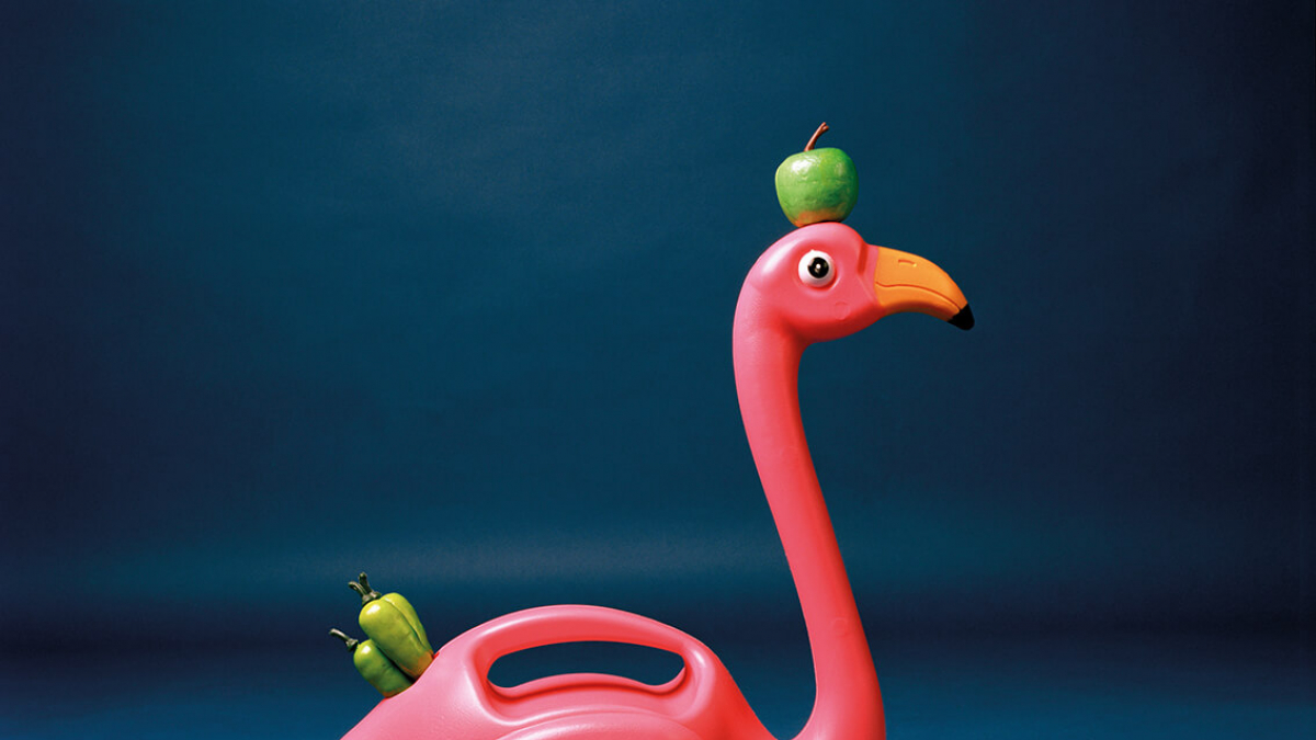 A pink plastic flamingo with a green apple on its head