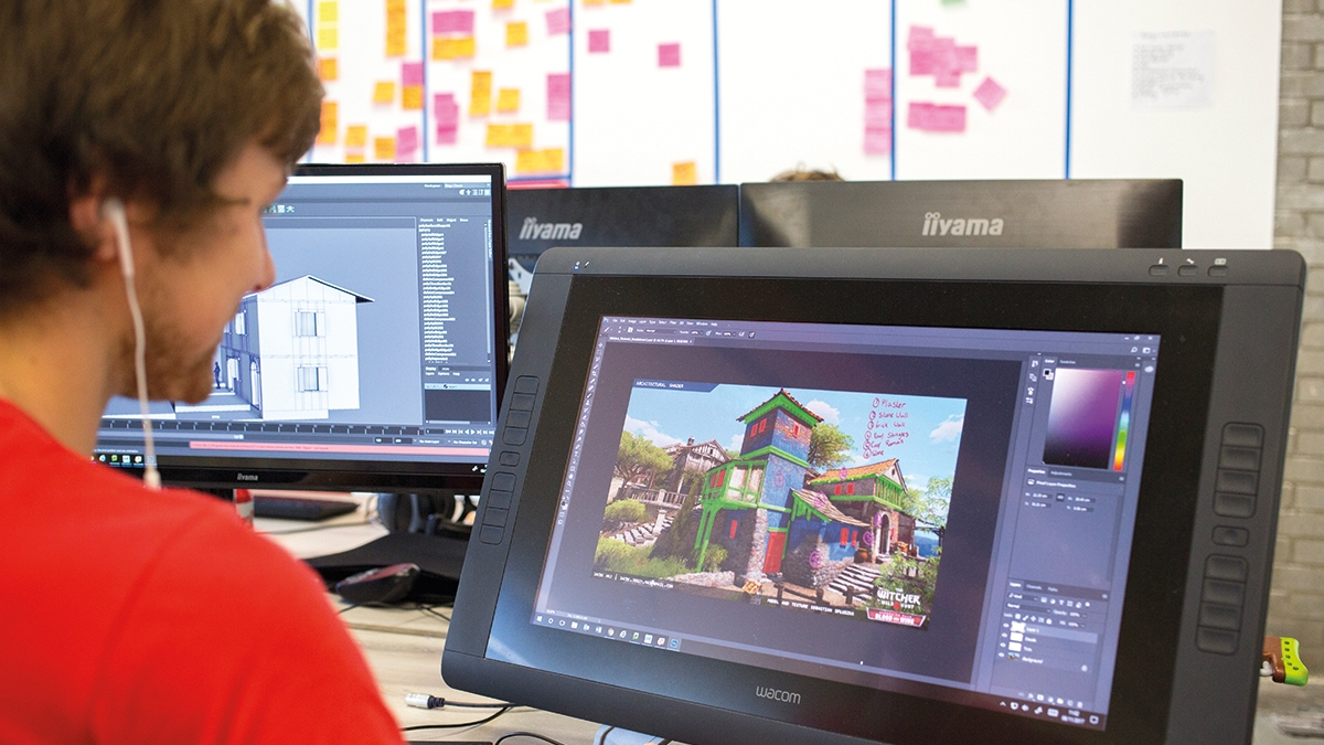 Games student with earphones and red t-shirt working at graphics tablet and creating an oriental building.