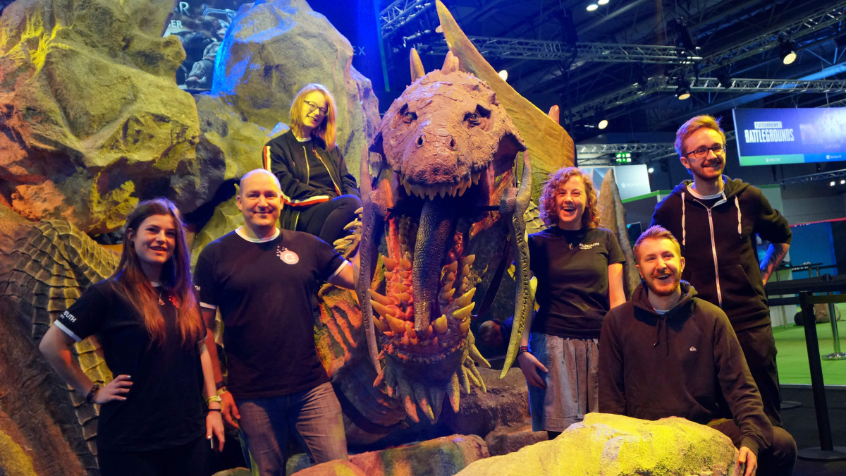 Falmouth University Games Academy students standing in front of a large dinosaur model
