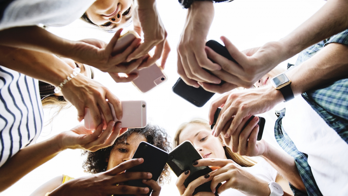 Young people using their phones in a circle
