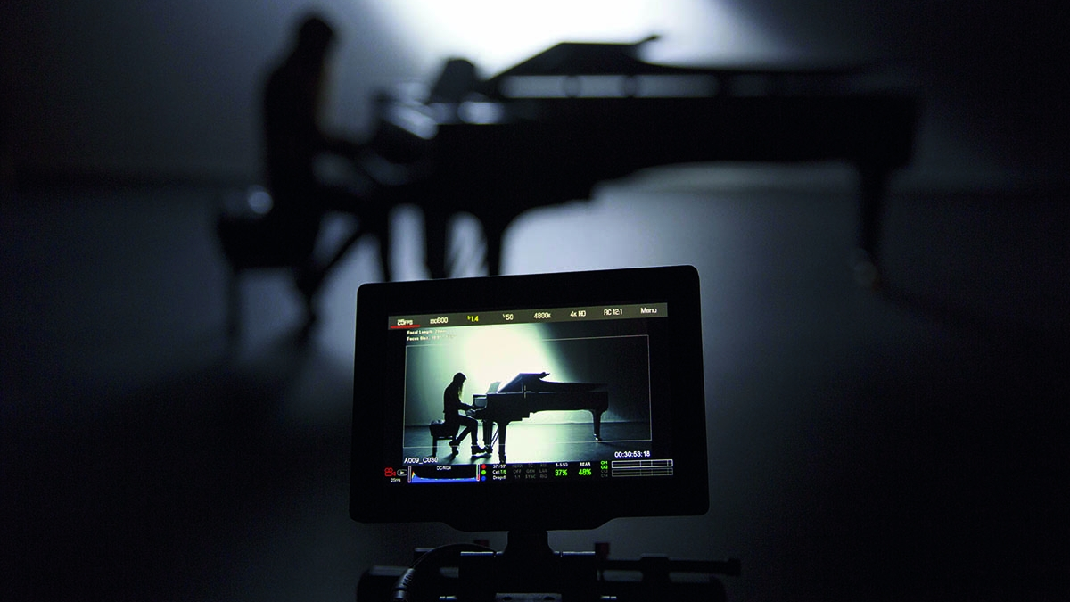 Student on a grand piano and the image on a camera viewfinder in the foreground.