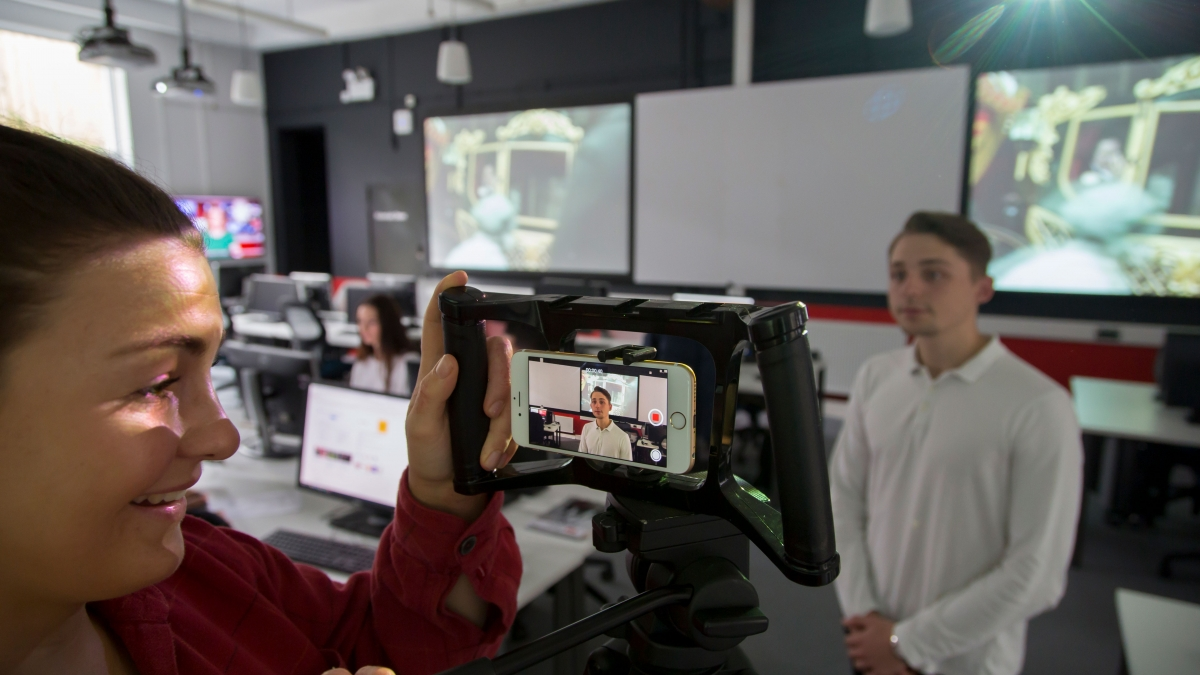 Students filming interview in newsroom.