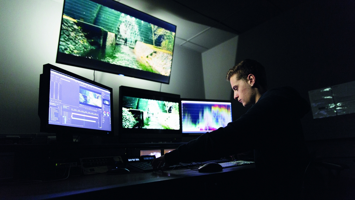 Student working in front of screens in editing suite.