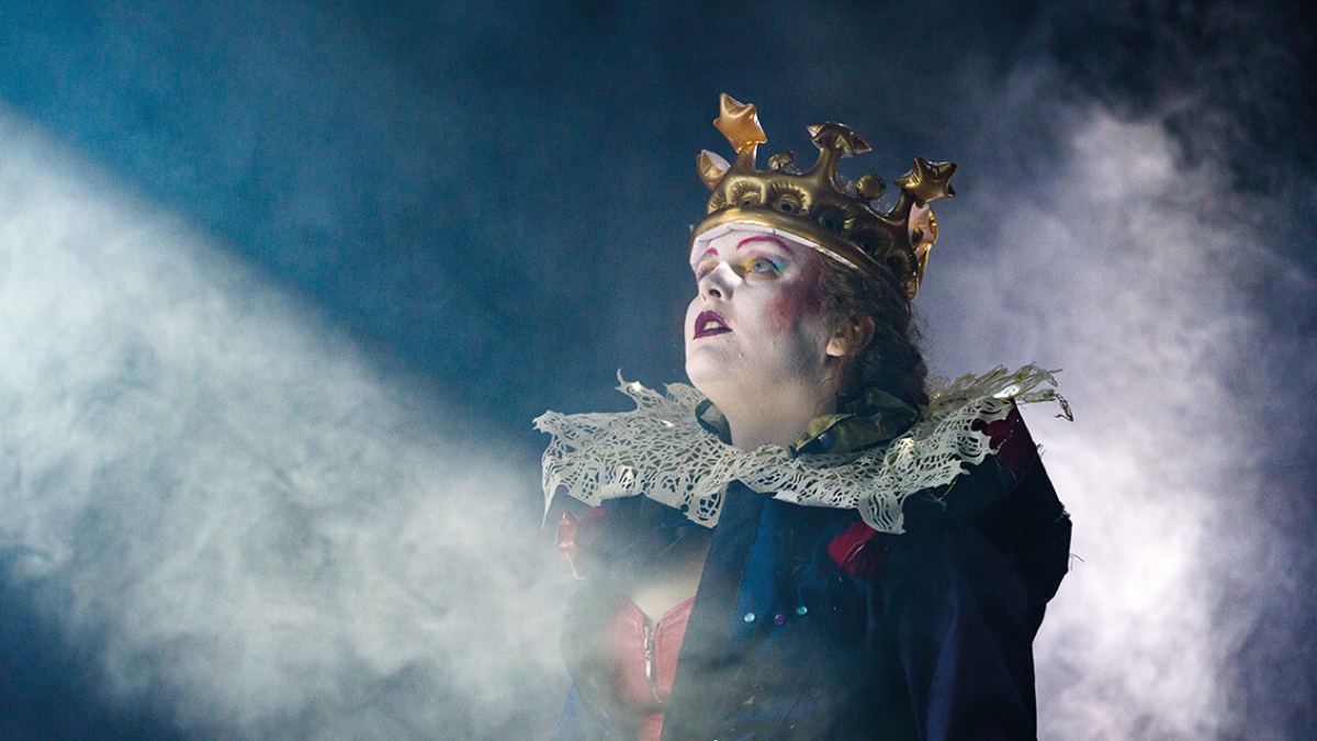 A Musical Theatre actor in stage makeup, wearing a ruff and crown