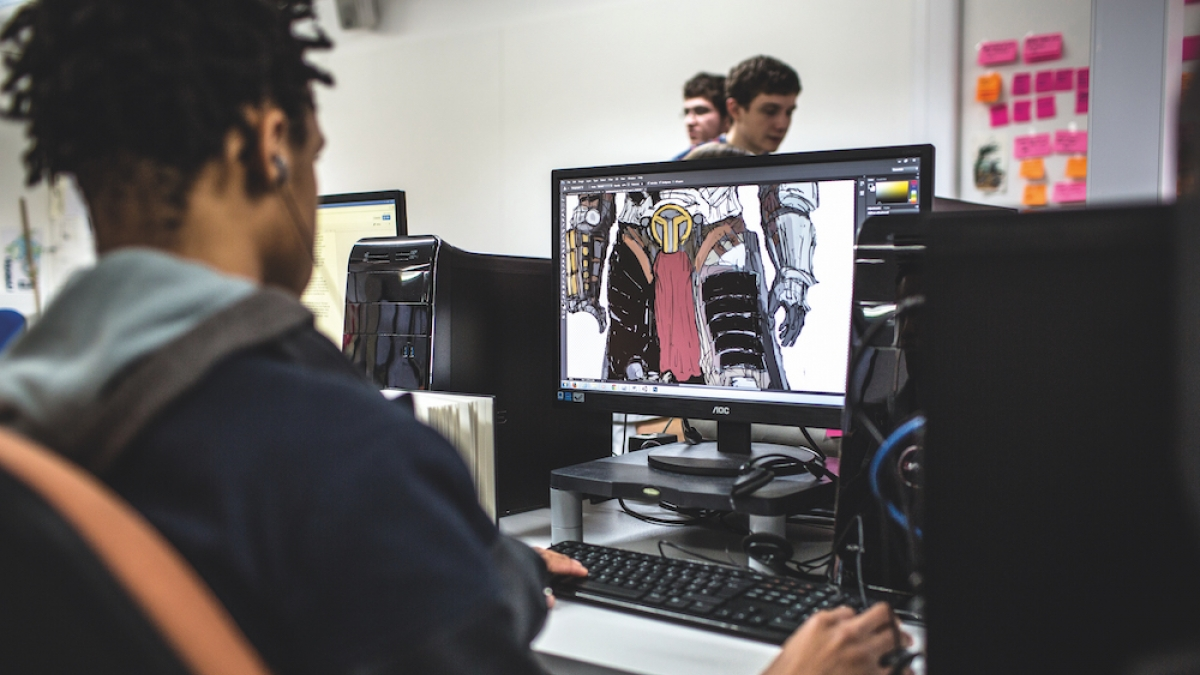 student seated at a desktop with game illustration on the screen