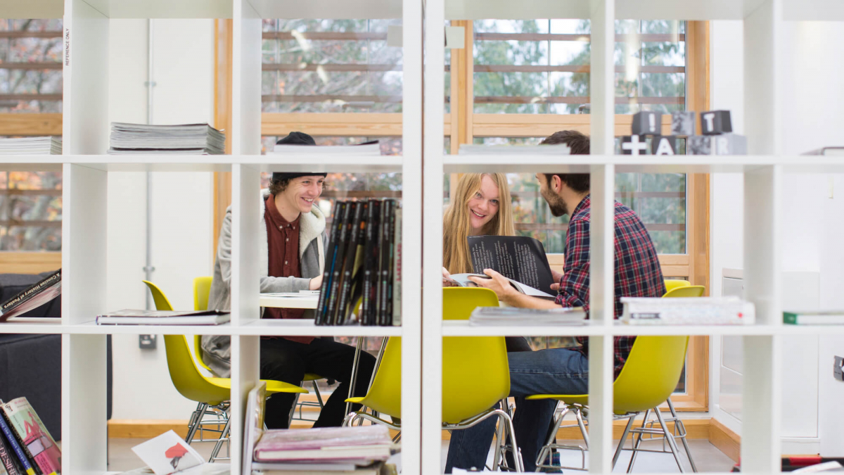 Students viewing through a square shelving unit.