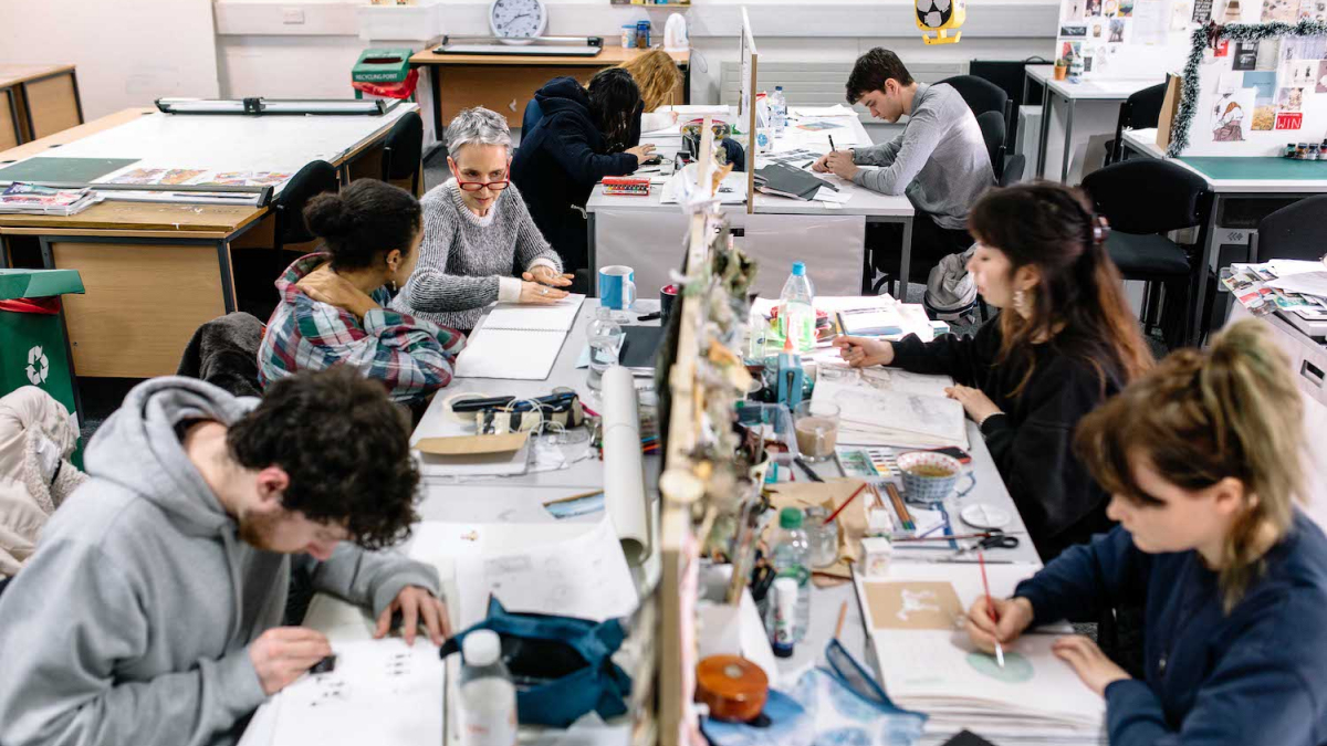Illustration students in busy studio at desks drawing.