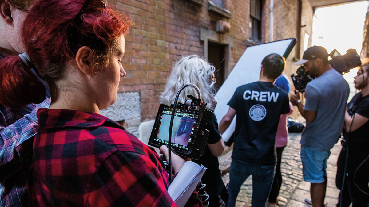 A group of Television students on a television production set with a camera