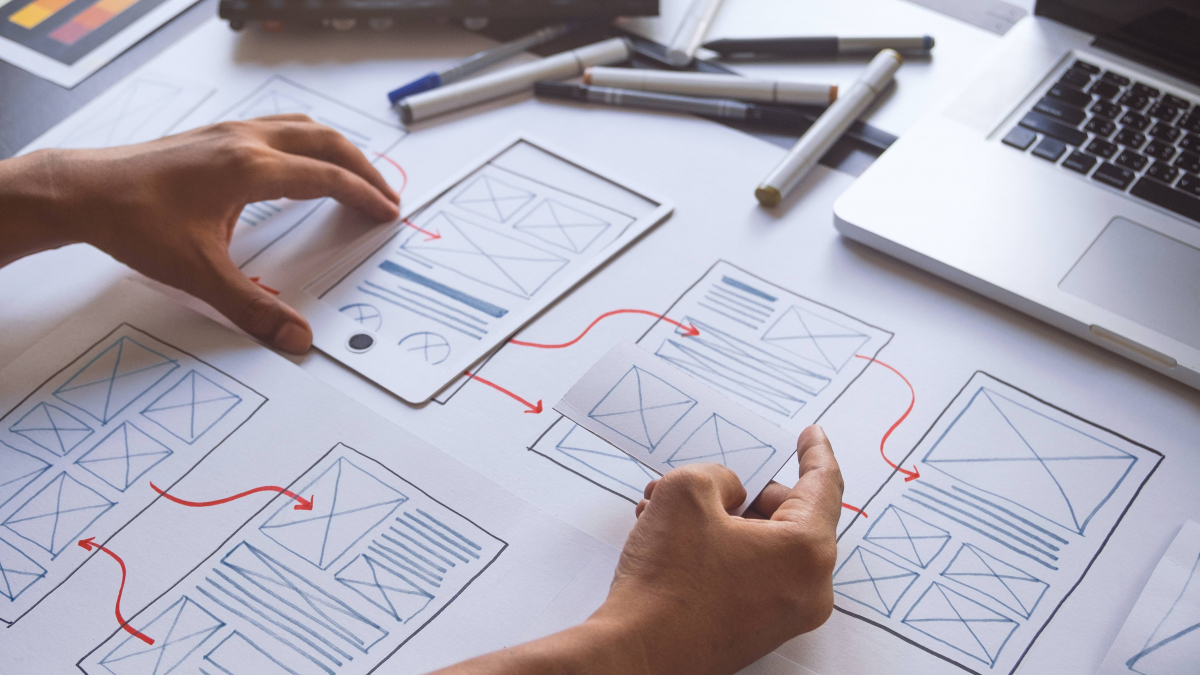 website layout plans on paper with hands and pens