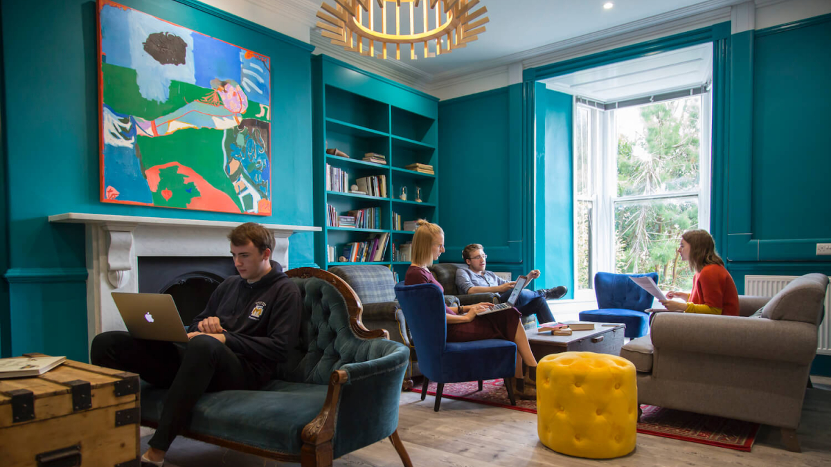 Falmouth University students sitting on armchairs and sofas in a teal room with wooden floor