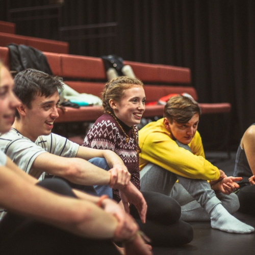 Group of students sat on theatre floor and smiling.