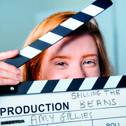 Student, Amy Gillies, peeking though a clapperboard.