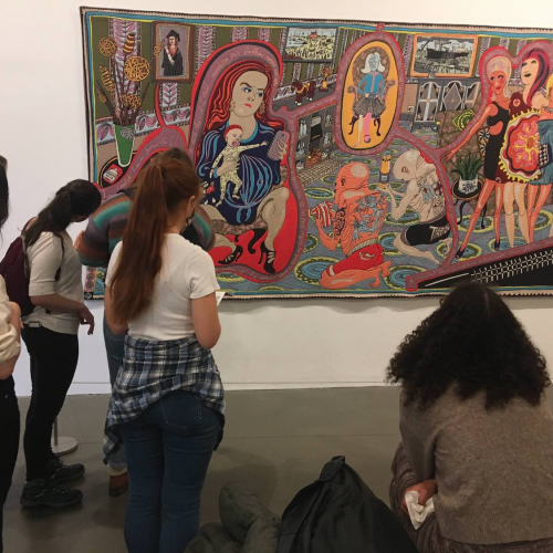 Falmouth University Illustration students looking at a large tapestry by artist, Grayson Perry