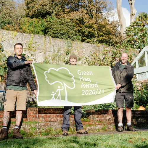 Three people holding up a banner in gardens