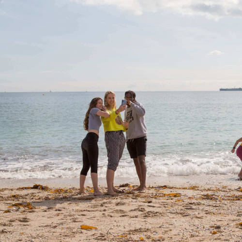 Five Falmouth University students on a sandy beach with the sea in the background