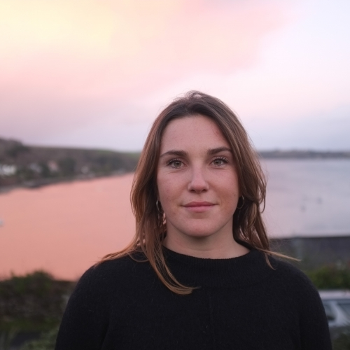 Head shot of graduate Jess Fairlie, with sea view in background