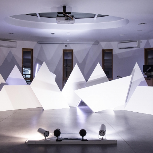 White triangle sculptures in a room lit with purple light