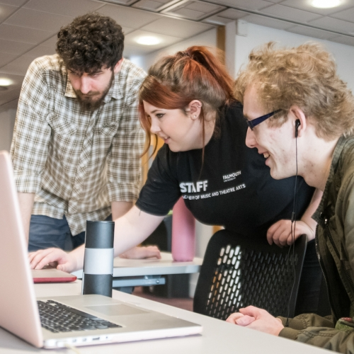 Three students around laptop