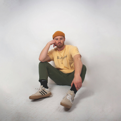 Sustainable Product Design student sitting on the floor wearing an orange hat and yellow tshirt