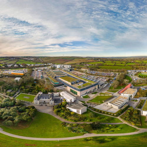 A wide angle aerial shot of Penryn campus with buildings and fields.